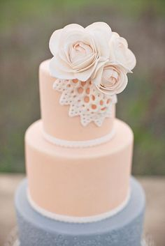 Three tier, bottom tier different color, top two tiers same color, simple doily and flower decoration.