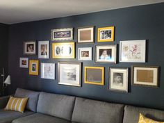 Wall of photo frames, yellow, grey, grey couch, yellow pillows - wall of photo frames with yellow/grey theme - family room