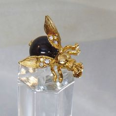 This #vintage trembler bee brooch is fabulous!  It features a gold tone metal flying insect or bee with clear rhinestone jewel encrusted wings and a black Lucite cabochon bo... #ecochic #etsy #jewelry #jewellery