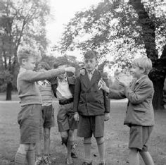 Playing Conkers in Regents Park. A traditional children's game played in the autumn, where the seeds of horsechestnut trees known as conkers, are threaded onto strings. Players take turns to swing their conkers into each other until one breaks and the remaining conker is the winner. c 1955 by Henry Grant.
