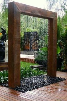 Tropical Landscape/Yard with Arbor, Water feature, Custom Glass Walls, Palm Sized Black Polished Rocks