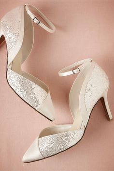 """High-Shine Heels, A classic pointed toe gets dressed up with panels of ivory satin and soft white glitter on this pair from Menbur. Perfect for dancing, the ankle strap keeps these lovelies in place and a medium heel means they'll be comfortable all night long. Buckle closure. Satin, glitter upper; synthetic sole. 3"""" satin wrapped heel. Imported."""