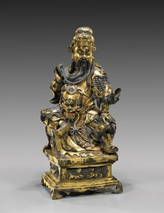 """Elaborate Chinese, Ming-style gilt bronze figure; of Guandi, dressed in elaborate armor with a lion mask to the front and a dragon headdress; seated in a very assertive pose, on a raised pedestal base with lotus and qilin panels; H: 15 1/2"""""""