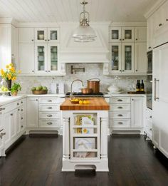 Beautiful white kitchen with marble, butcher block countertop on island, and dark wood floors.
