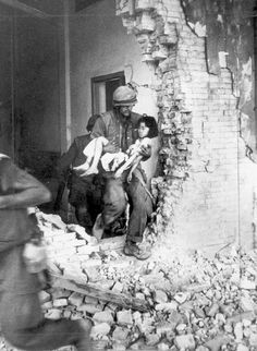 A US Marine carries a seriously wounded Vietnamese child from the ruins of a home in Hue. - Douglas Pike Photograph Collection