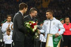 Lukas Podolski of Germany stands with DFB President Reinhard Grindel  and  Dr. Friedrich Curtius prior to his final game for Germany before the international friendly match between Germany and England at Signal Iduna Park on March 22, 2017 in Dortmund, Germany.
