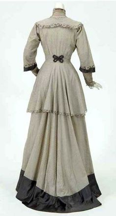 Day dress, Spettel Sisters, Saint Paul, MN, ca. 1907-11. One-piece gray dotted cotton with gray satin trim. Standing lace collar, full-length sleeves with lace below elbow, natural waist. Separate underskirt is brown polished cotton with a flounce of gray satin. Minnesota Historical Society