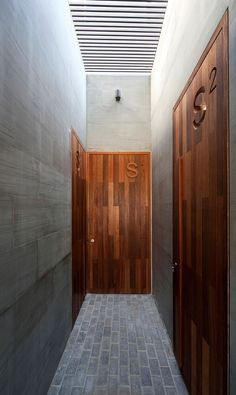 Wood and grey stone, top lit corridor. The S Cube Chalet by AGi Architects.
