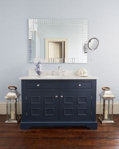 Farrow & Ball's Hague Blue give this bespoke bathroom vanity cabinet by Barnes of Ashburton a cool, masculine feel. Carrara marble top completed this luxurious look.