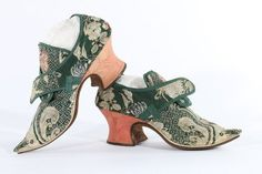 * Pair of brocaded silk shoes, 1721, of dark green and ivory silk brocade woven with pink and blue carnations, edged in green braid, with white leather rand, pink damask heels, sharply pointed toes, lined in soft tan leather, the tongues backed in Chinese-yellow silk