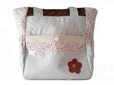 Bolsa em tecido com aplicações, possui bolso frontal com fecho de botão forrado, bolsos laterais com elástico, bolso interno e fechamento de zipper.
