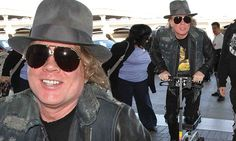 Axl Rose uses scooter to support broken foot as he hobbles through LAX