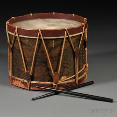 "ELI BROWN, DRUM MANUFACTURER, HAS CONSTANTLY FOR SALE BASS AND SNARE DRUMS/MADE IN THE NEATEST AND BEST MANNER/Windsor (Wintonbury Soc.) Conn. 1833 No. 1712.""; with red-painted hoops, later ropes and leather ears, accompanied by a later pair of drumsticks, 13 1/2, dia. 17 1/2 in.     Note: Eli Brown descended in a family which settled in the Windsor, Connecticut, area, and whose ancestors served in the Revolutionary War. The Browns of Wintonbury were mainly subsistence farmers"