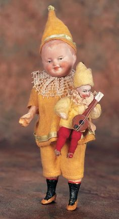 Super cute little bisque head boy in original felt clown costume and holding a mini version of himself... approx. 1920-30
