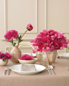 Fuchsia Centerpiece  Fuchsia peonies, sweet peas, and anemones housed in vessels of various styles and materials pop against a sandy backdrop.