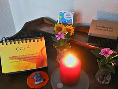 Our table of inspirational quotes at the entrance of our home.  Timeless calendar with a quote for everyday, children's positive thinking cards and children's affirmation cards.  Table dressed with candle, flowers and semi-precious rock (amethyst and rose quartz).