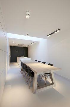 hier zie je een duidelijk beeld van een eettafel die wordt verlicht door spotjes, ook zie je een robuuste tafel met simpele stoelen