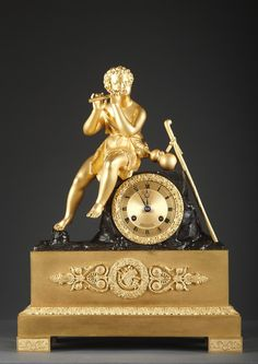 A gilt and patinated bronze mantel clock. The dial is contained in a rock on which sits a shepherd playing the flute. The base is adorned with a...