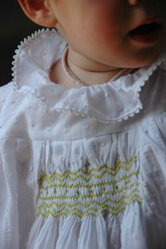 Smocked baby dress on embroidered fabric.