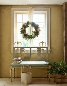Dining Room Wreath    A Scandinavian-style wreath of boxwood and dried wheat hangs above a 19th-century painted-wood bench in Edie van Breems's dining room.