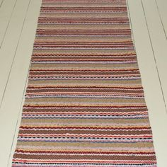 A long rug made from deeper colours such as browns and reds. It's overall condition is good but has come slightly loose at one end. If wanted, it can be unpicked and re-knotted. 100% Cotton, dry cleaning recommended.