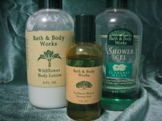 """In 1990, the first Bath and Body Works lotions were about 6"""" tall and were 8 ounce bottles with green flip top caps with laminated, off white colored labels. The first logo before the sunrise was a tree. Also shown for comparison was the next logo with the long ray sunrise inside of a green, rectangular box. Notice how the scent names representations were changed as well."""