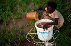 A girl collects water from a puddle at the flooded Jamam refugee camp in South Sudan's Upper Nile July 1, 2012. REUTERS/Adriane Ohanesian