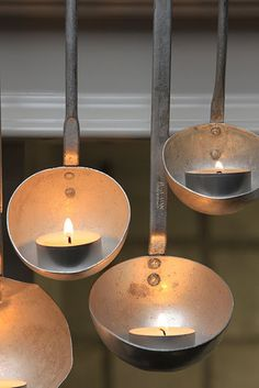 Hanging metal ladles hold tealight candles