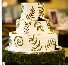 Ivory buttercream frosting accented with various shades and varieties of ferns...moss, leaves, and pinecones on the cake's base create a rustic feel.  from Classic Cakes of Carmel.
