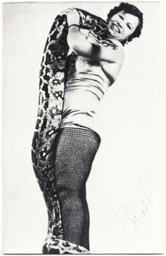 A real photo postcard of snake charmer Ada Mae Salo with a boa. This postcard was probably published in the 1960s or 1970s.