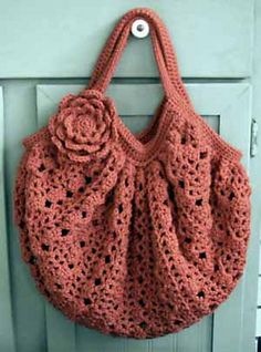 You can crochet a slouch bag by simply making a rectangle using any stitch or motif that has good drape and flexibility. Crochet rectangle, gather using hdc or sc, crochet handles, add flower. This stitch is  #370 from The Complete Book of Crochet Stitch Designs. The flower is an Irish rose.