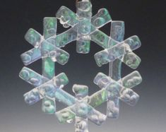 Fused iridized clear glass snowflake developed and formed by me, and arrives in its own decorative keepsake gift box. Ready to hang as an ornament or sun catcher from clear floss and a stainless steel wire hoop fused in the glass. Each Snowflake Sold Separately. Like real snowflakes, no two are alike! Each iridized snowflake has individual variations – the colors and forms blend together for a unique art decoration. If you have any questions, please contact me. This item has been…