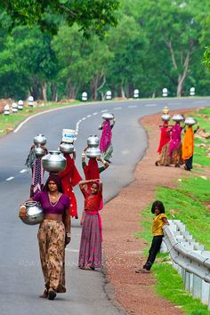 The Water Bearers , India. As evening falls, women from from a hill top village come down to the road to fill water from a well. These women make several trips a day expertly balancing nearly 20 liters of water in a go.