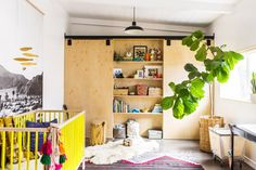 A non-traditional, amazing nursery with built-in bookshelf, fiddle leaf, and yellow crib