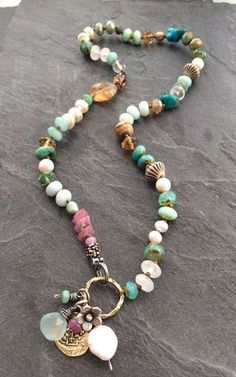 Colorful multi charm Colorful multi charm necklace by mollymoojewels. A mix of semi precious beads, including moonstones, pearls, turquoise, amazonite, jasper, raw ruby, sapphires and Czech glass in hues of blue, Aqua and pink. Adorned with sterling silver accents, a sterling flower charm, an artisan bronze replica of an ancient coin and wire wrapped briolettes The necklace is designed to fasten at the front with a sterling lobster clasp. Length is approx 21.5 including the charms. ..