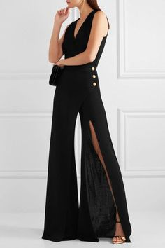 BALMAIN Embellished wrap-effect stretch-knit jumpsuit $2,835 Balmain captures the glamour of an evening gown and the comfort of a jumpsuit with this stretch-knit design. Crafted in a relaxed silhouette, this figure-skimming style has a V-neckline and a split that scores right up to the thigh. Complement the label's signature embossed buttons with gold jewelry and heels.  Shown here with: Saint Laurent Shoulder bag, Giuseppe Zanotti Mules, Jennifer Fisher Ring, Chloé Earrings.