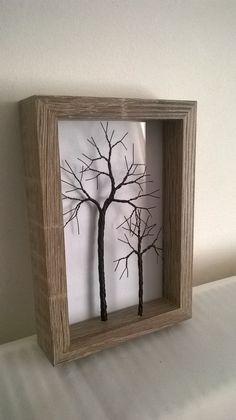 Árbol pequeño de alambre torcido en un marco rústico.