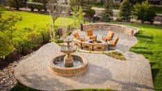 This terraced stone patio provides multiple outdoor entertaining areas with a view. Guests are led down a path to the formal stone water feature which picks up on textures used throughout the garden. A comfortable seating area surrounds a custom stone fire pit and is framed by a soft green lawn and a curved stone wall.