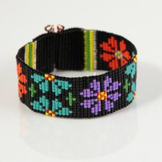 SALE! Was $36, now only $26!  This Colorful Flowers Beaded Cuff bracelet was inspired by the bright and beautiful patterns I see around me here in Albuquerque, New Mexico. As with all my pieces, Ive created it on a bead loom with great care and attention to detail. The beads used in this piece are my favorite - high quality glass Japanese Delicas, much more even and consistent than the beads most commonly used in loom work. This piece includes red, orange, yellow, black, turquoise, orange…