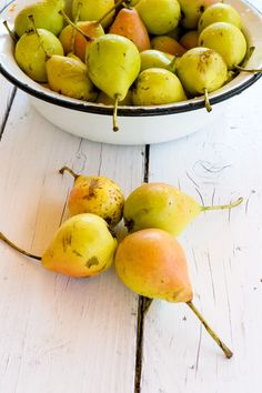 Pears - Pile of fresh and ripe pears in a metal bowl on white wooden table