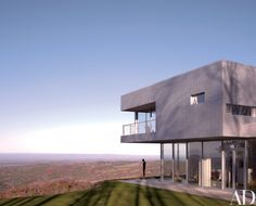 For the Hudson Valley, New York, getaway of Mary and Sean Kelly, Toshiko Mori Architect stacked an upper story clad in aluminum-foam panels atop a glass-walled ground floor. The cast-iron figure is Antony Gormley's sculpture You.