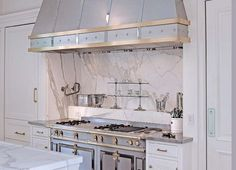 A stainless steel french stove under a marble spice shelf and a stainless steel range hood with brass trim flanked by recessed paneled refrigerators and stacked freezer drawers.