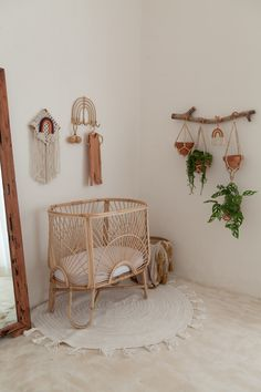 Baby room with rattan crib and plants hanging from the wall.