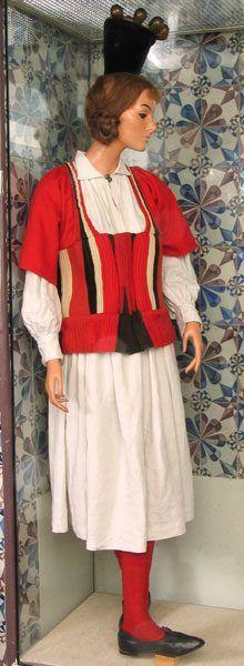 Rückenteil ist vollständig aus schwarzem Wollplissé (Köperbindung). Um Umfang noch zu erweitern, ist in Mitte ein Keil aus Plissé eingenäht. Vorderteil ist gerade geschnitten und setzt sich aus 3 Teilen zusammen: Taillenbund (L:12cm), Leibchen (L:22cm) und Ärmelansatz (L:30cm). 4 verschiedene Stoffe (feiner Wollfilz rot-1, grober Wollfilz rot-2, schwarzer Samt, naturweißer grober Wollstoff in Leinwandbindung) und der Plissé sind so Falten gelegt, daß sich eine Rippenstruktur bildet. usw…