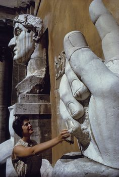Tourist touches fragments of colossal head and hand of Constantine in Rome, December 1962. PHOTOGRAPH BY ROBERT SISSON, NATIONAL GEOGRAPHIC