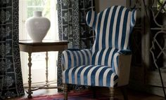 William Yeoward - Marlena and Alberesque Fabric Collection - A grand blue and white striped armchair beside navy patterned curtains, with a painted wood side table and a white vase Wingback Chair, Armchair, Living Spaces, Living Room, Curtain Patterns, Bedroom Chair, Roman Blinds, White Vases, Painting On Wood