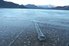 """Racetrack Playa is home to an enduring Death Valley mystery. Littered across the surface of this dry lake, also called a """"playa,"""" are hundreds of rocks – some weighing as much as 320 kilograms (700 pounds) – that seem to have been dragged across the ground, leaving synchronized trails that can st..."""