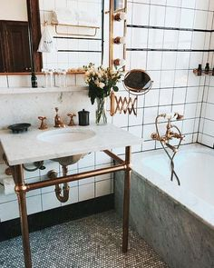 dark floor, white walls, brass/gold accents, console sink