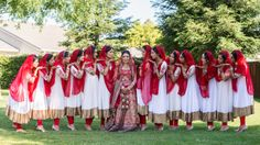 Indian Sikh wedding bridesmaids in white salwar kameez suits with gold borders and red dupattas
