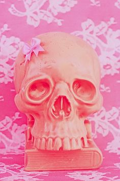 Pink skull with bow, lace background, and book.